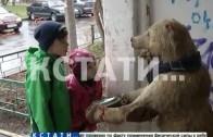 Нищий медведь выпрашивает милостыню у подъезда девятиэтажного дома